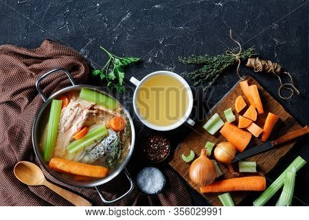 Fish Broth Or Soup Of Salmon, Onion, Carrot, Celery, Herbs And Spices In A Stockpot And In A White B