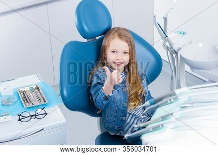 Little Cute Girl Is Sitting In Dental Blue Chair In Clinic, Office With Tools, Instruments. Smiling