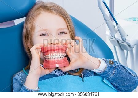 Little Cute Girl Is Sitting In Dental Blue Chair In Clinic, Office. Funny Kid Patient Is Holding Jaw