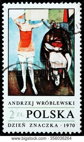 Luga, Russia - October 15, 2019: A Stamp Printed By Poland Shows Painting Woman Hanging Up Laundry,