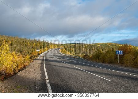 Kola Highway, Kola Peninsula, Murmansk Region. Northern Country Road Among Hills With Colorful Autum