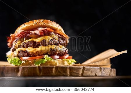 Juicy Burger On The Board, Black Background. Dark Background, Fast Food. Traditional American Food.
