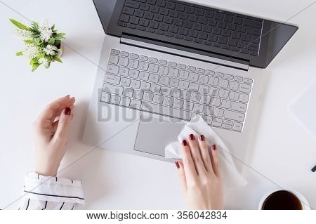 A Woman Worker Cleaning With Antivirus Wet Wipe A Laptop And A Working Office Desk Before Starting W