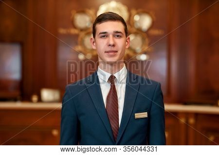 Close Up Of Happy Male Receptionist Worker In Uniform Looking At Camera With A Smile While Standing