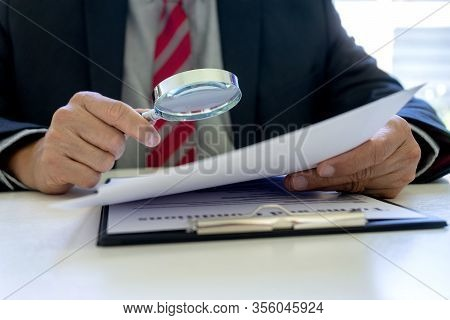 Lawyer Or Judge Use Magnifier Glass Look To The Paper