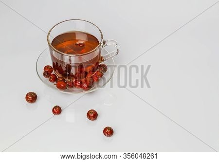 Rose Hip Flower, Dried Rose Hip Fruit And Glass Cup With It Infusion On White Wooden Background.