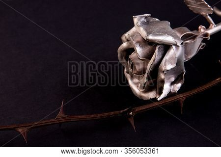Metal Rose On A Dark Background With A Branch With Spikes, Concept Symbol Of Stamina, Courage, Faith