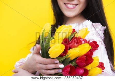 Mothers Day. A Large Bouquet Of Tulips Close-up In Female Hands.