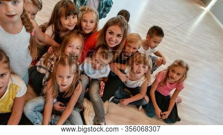 Happy Female Dance Trainer With Positive And Cute Children Looking At Camera And Smiling While Sitti