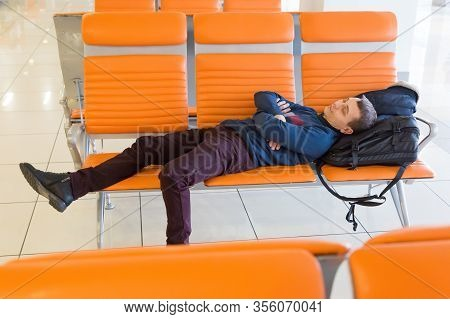 A 35-40 Year Old Man Sleeps On A Bench While Waiting For His Flight At The Airport.