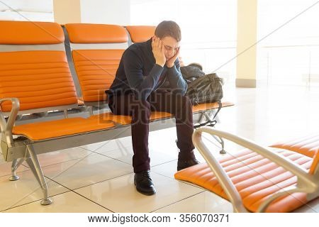 A Passenger Is Waiting For His Plane At The Airport. A 35-40 Year Old Man Sleeps A Bench While Waiti