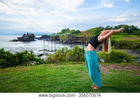 Young Woman Practicing Yoga, Standing In Hasta Uttanasana Pose. Outdoor Yoga On The Cliff. Raised Ar