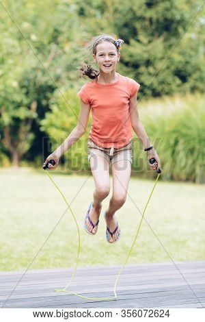 Laughing Teenage Girl Jumping Rope In The Garden On The Terrace In Summer