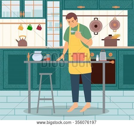 Man In Apron Standing Near Pan And Eating From Spoon. Interior View Of Kitchen With Kettle And Boili