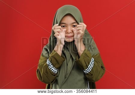 Young Beautiful Muslim Woman Wipe Her Tear. A Young Muslim Woman Is Crying. The Girl Wipes Her Tears