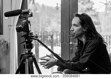 A Side Profile View In Black And White Of A Professional Documentary Maker Sitting Indoors With Dslr