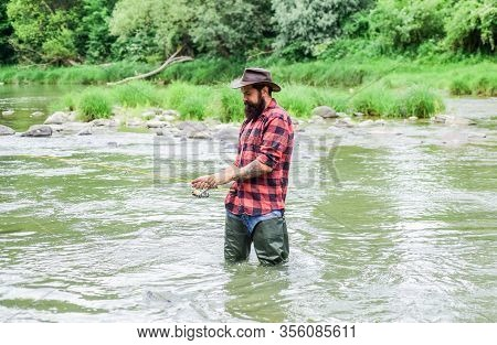 Brutal Man Wear Rubber Boots Stand In River Water. Satisfied Fisher. Fishing Requires You To Be Mind