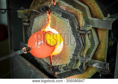 A Close Up Shot During The Production Of A Blown Lantern, A Blowpipe And Molten Glass Is Heated In A