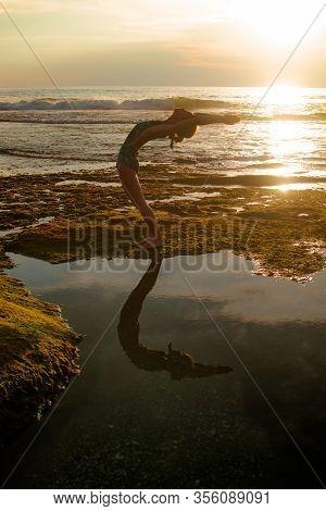 Outdoor Sunset Yoga. Attractive Woman Standing In Hasta Uttanasana Pose, Deflection Back. Yoga Retre