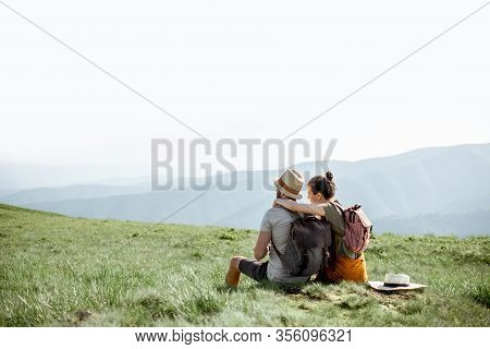 Young Couple Sitting On The Green Meadow, Traveling With Backpacks In The Mountains During The Summe