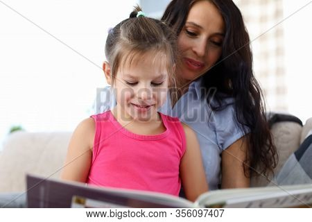 Portrait Of Smiling Child Looking At Book With Interest. Happy Woman Teaching Daughter To Read. Litt