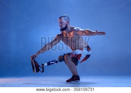 Athlete With Disabilities Or Amputee Isolated On Blue Studio Background. Professional Male Sportsman