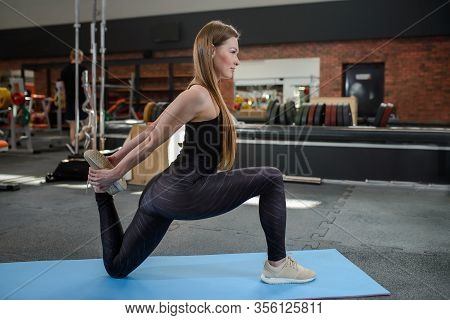 Portrait Of Fitness Woman Stretching At Gym Before Workout. Leg Stretches. Sports Activity, Healthy