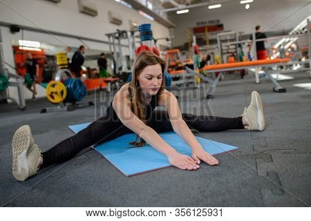 Fitness Woman Stretching Legs Sitting On Gym Mat. Soirt, And Healthy Lifestyle.