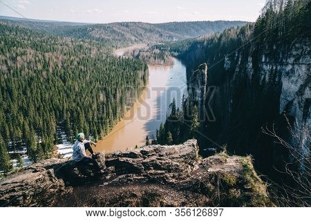 Man Traveller Sitting Near Edge Of Cliff Looking At Beautiful Spring Landscape