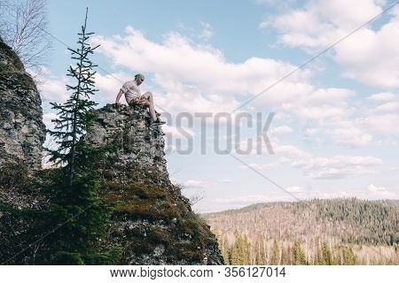 Young Hiker Looking Down From A Top Of A Mountain