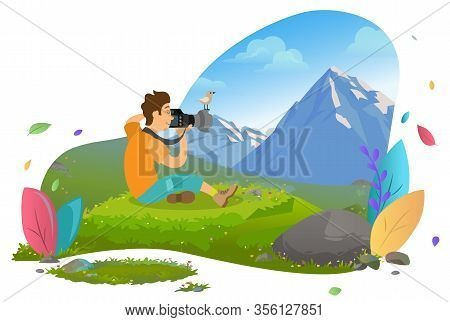 Tourist Man Sitting On Grass And Taking Photo Of Mountain Landscape. Little Bird On Top Of Camera Le