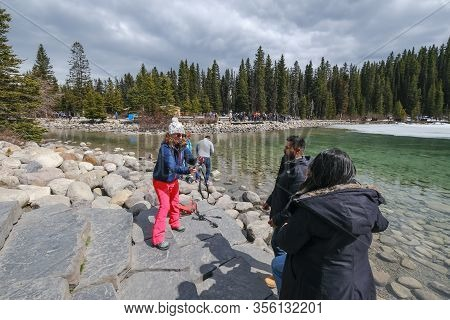 Lake Louise - May 20 2019: Lake Louise, Alberta, Canada. Girl Taking A Picture Of A Couple At Lake L