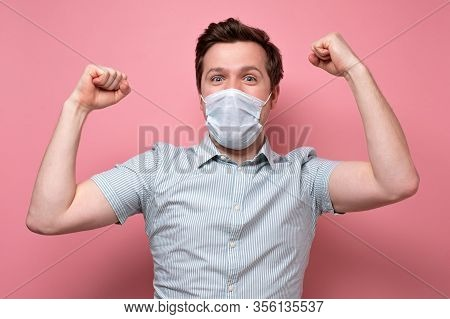 Caucasian Young Man Holding Fists Up Being Happy With Recovery Wearing Medical Mask
