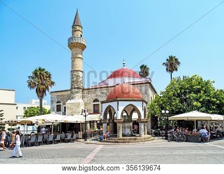 Kos, Greece - July 31, 2015: People Sitting In A Cafe In Front Of The Deterdar Mosque In Kos Town (g