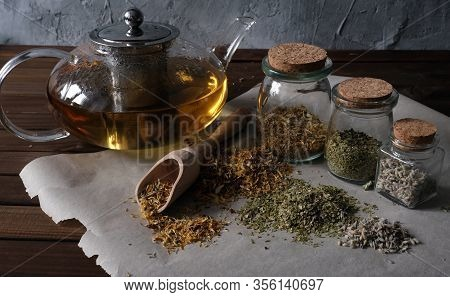 Homemade Apothecary. Natural Herbs Medicinal. Dried Herbs In Glass Jars And Teapot On Dark Wooden Su