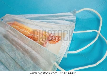 Face Masks And Banknote Of 5000 Rubles On Blue Background. Concept Of Deficit, Speculation And Sold