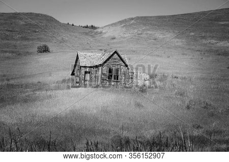 Black And White Pioneer Homestead.  An Old Pioneer Home With Broken Windows And Abandoned Piece Of H