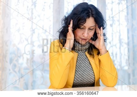 Middle Aged Woman Holding Her Head. Looking Stressed