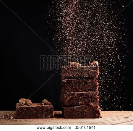Stack Of Square Baked Brownie Pieces Sprinkled With Cocoa Powder, Particles Froze In The Air Against