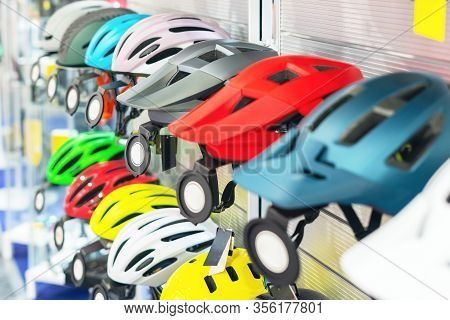 Bicycle Helmets On The Counter In The Bike Shop.