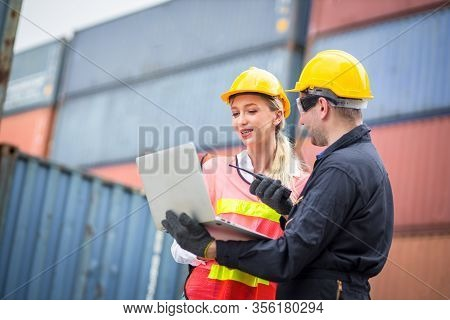 Female Dock Worker Wearing A White Helmet Yellow Standing In A Industrial Shipping Yard She Discussi