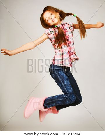 little girl jumps on a gray  background