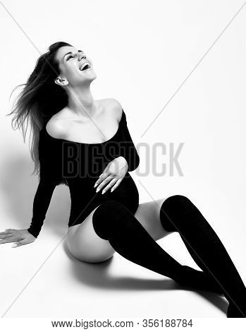 Pregnant Mom In Black Leotard And Stockings. She Put Hand On Her Belly, Laughing, Sitting On The Flo