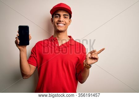 Young handsome african american delivery man holding smartphone showing screen app very happy pointing with hand and finger to the side