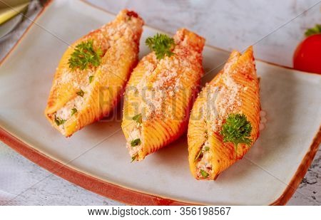 Pasta Shells Stuffed With Ricotta, Meat And Parmesan On Plate With Parsley. Close Up.