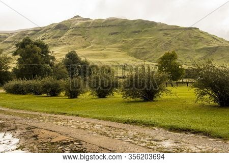 Grass Covered Mountain With Concrete Tracks In Foreground