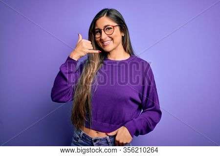 Young beautiful smart woman wearing glasses over purple isolated background smiling doing phone gesture with hand and fingers like talking on the telephone. Communicating concepts.