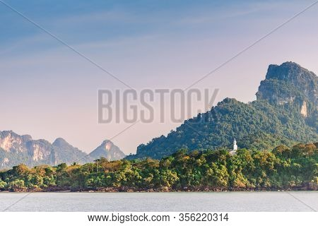 The Statue Of The White Buddha Towers Over The Jungle. Buddha On The Background Of Picturesque Mount