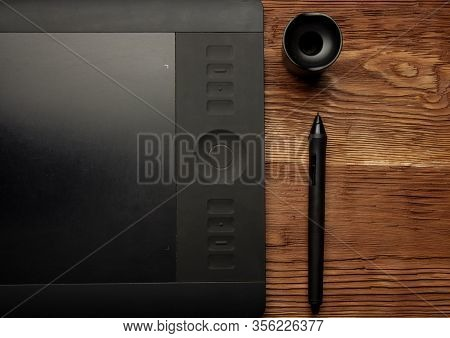 Black Graphic Tablet Lie On A Brown Wooden Background Photo