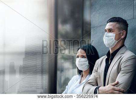 Covid-19 Or Corona Virus Situation In Business Concept. Businessman And Woman With Medical Mask Look